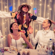 Vőfély női ruhában a menyasszony és a vőlegény mellett